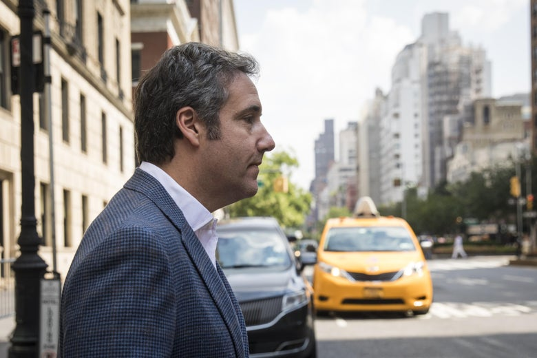 Michael Cohen walks on a New York City street in front of a yellow taxi cab.