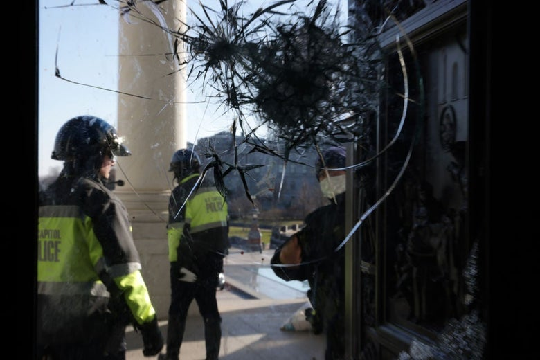 Two officers in helmets and fluorescent jackets are seen walking near a white column through a window that has been badly cracked by what appear to be multiple impacts.