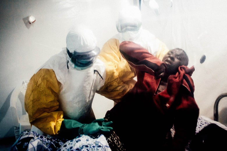 An Ebola patient is lifted up by two medical workers after being admitted into a Biosecure Emergency Care Unit on Aug. 15 in Beni.