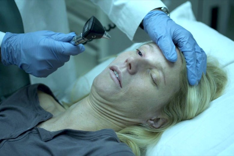 Gwyneth Paltrow (as Beth Emhoff) is examined by a doctor on a bed with an ophthalmoscope