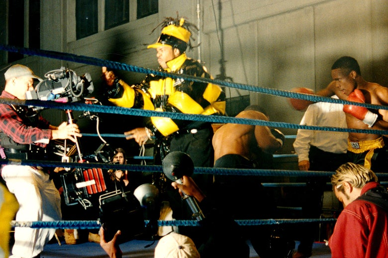 """Busta Rhymes, in a shiny yellow coat, films his part for the """"Rumble In the Jungle"""" video."""