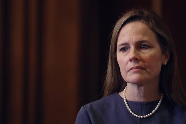 Amy Coney Barrett looks off to the side.