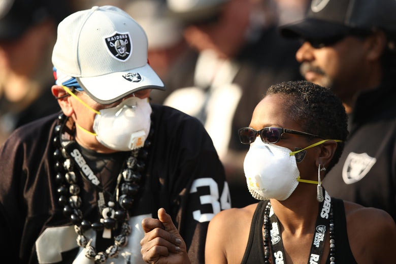 Two Raiders fans wear respirator masks covering their noses and mouths during an NFL game in Oakland, California.