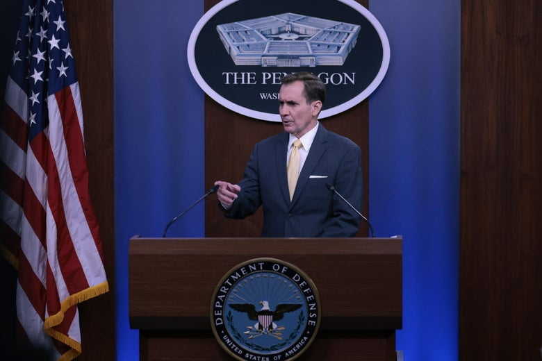 """John Kirby speaks at a DOD lectern, in front of a U.S. flag and a sign reading """"The Pentagon."""""""