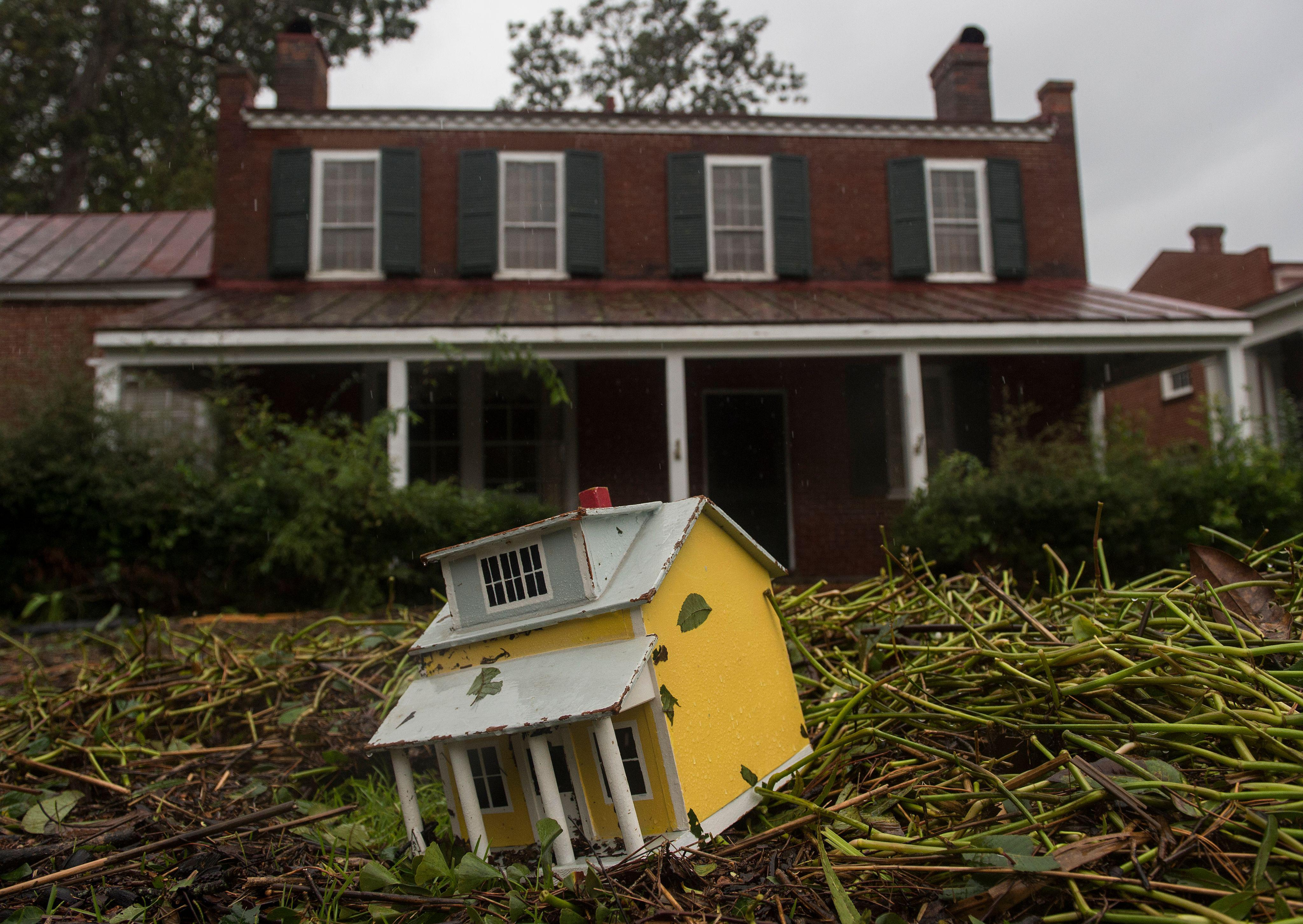 A toy house and other debris is strewn in the front lawn of a house, from flooding the day before when Hurricane Florence made landfal, in New Bern, North Carolina on September 15, 2018.