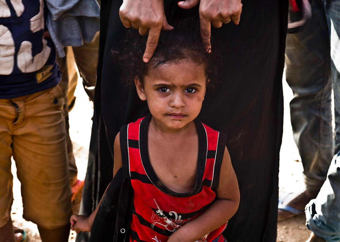 A child at the port awaits docking onto the boat to Yemen.
