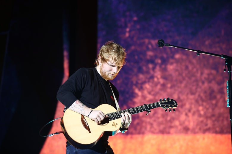 Ed Sheeran plays a guitar onstage in New Zealand