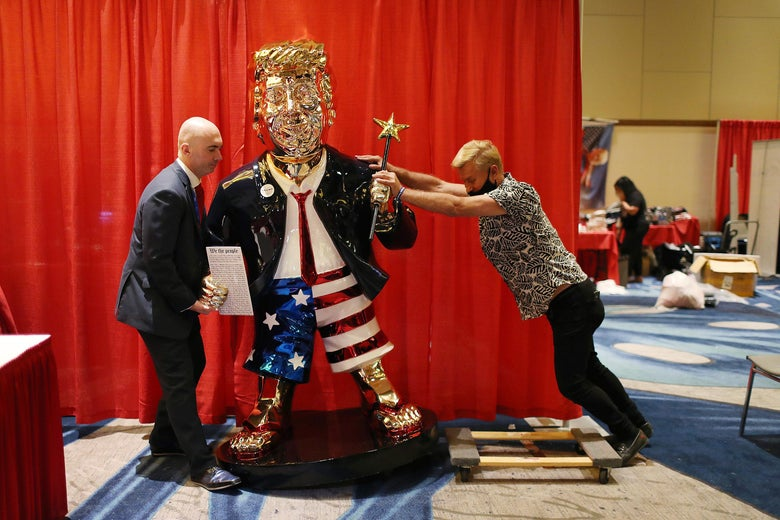 One man pushes one side of the golden Trump statue while the other man pulls from the other side. The statue depicts Trump wearing American flag shorts and holding a magic wand.