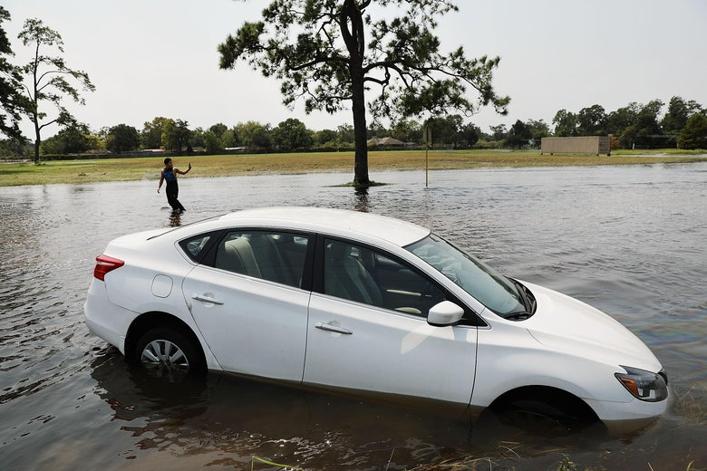 ORANGE, TX - SEPTEMBER 06:  Juan Aquinaga walks by a submerged car while going to check on his sister's house in Orange as Texas slowly moves toward recovery from the devastation of Hurricane Harvey on September 6, 2017 in Orange, Texas. Almost a week after Hurricane Harvey ravaged parts of the state, some neighborhoods still remained flooded and without electricity. While downtown Houston is returning to business, thousands continue to live in shelters, hotels and other accommodations as they contemplate their future.  (Photo by Spencer Platt/Getty Images)