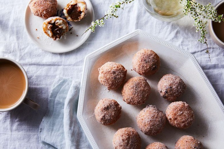 Ten brown, cinnamon-covered balls sit on an octagonal white plate. Three more are on a small, round white plate. There's a bite out of one, and you can see creamy brown Nutella inside. A cup of coffee with cream peeks in from the left.