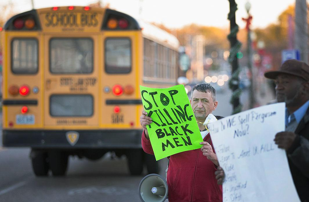 A school bus passes demonstrators protesting outside the police station on Nov. 10, 2014, in Ferguson, Missouri. As the suburb prepares for the grand jury decision in the shooting death of Michael Brown, school leaders have urged officials to announce the finding outside of school hours so that children will not be at risk of being caught up in rioting if it occurs. The grand jury's decision is expected sometime in November