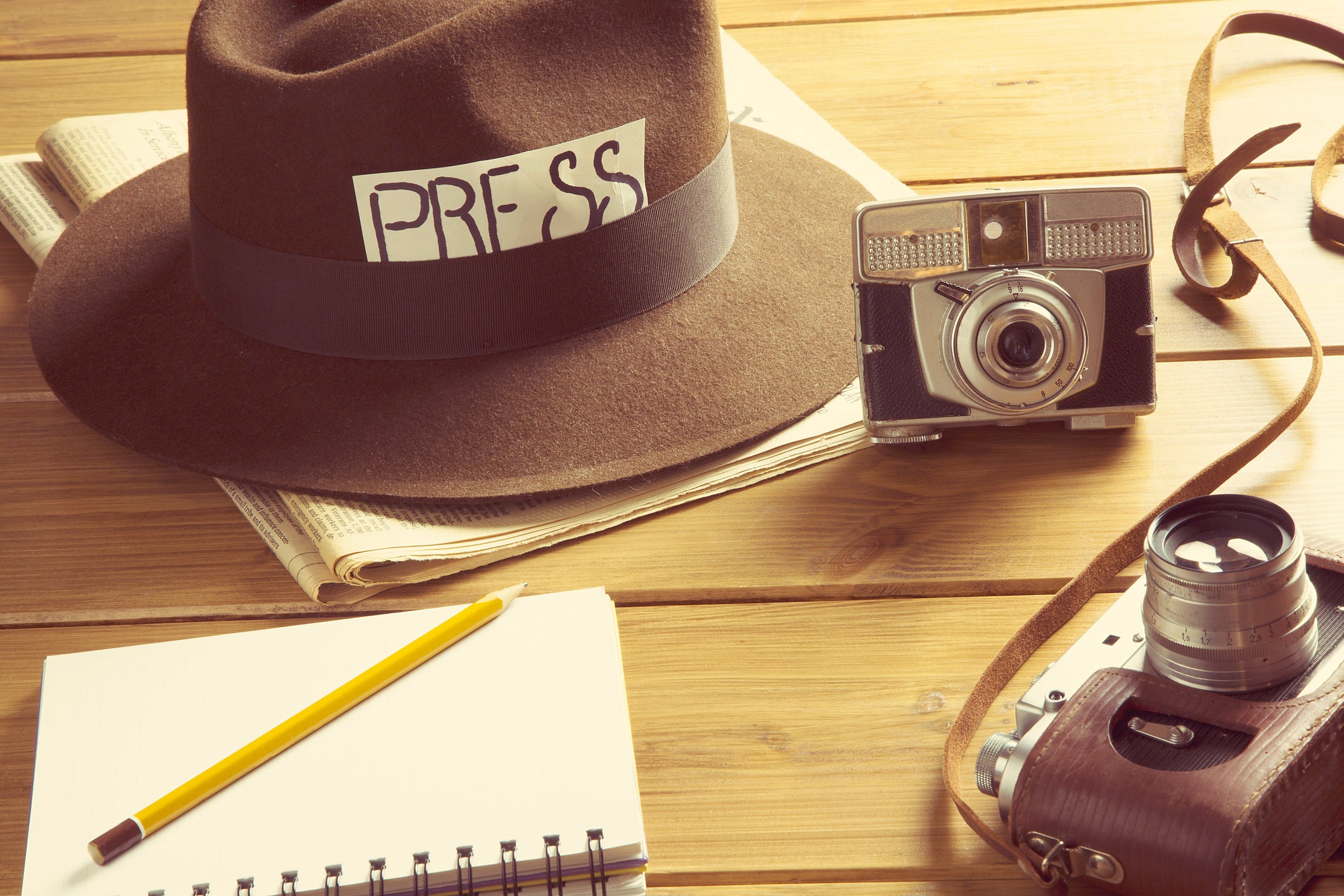 Journalism tools on a table, including a camera, notebook, and press hat.