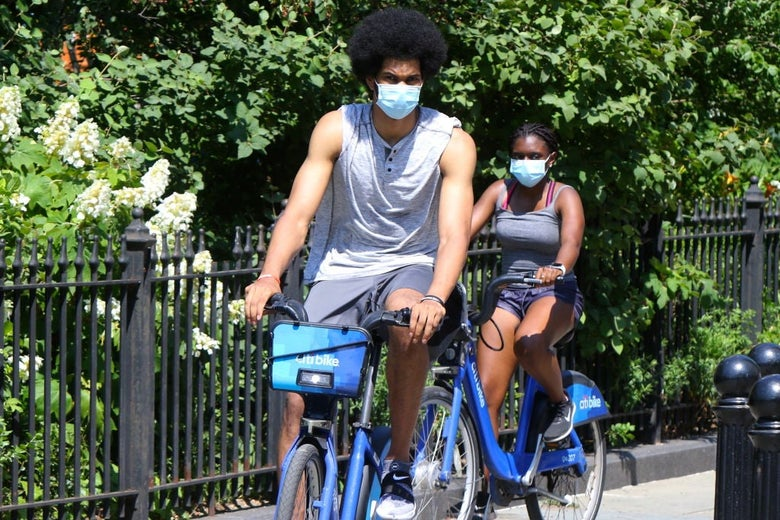 Allen, wearing a sleeveless shirt and a medical mask, rides a blue CitiBike on a path past a garden.