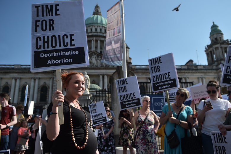 "Protesters hold signs saying, ""Time for Choice. Decriminalise Abortion."""