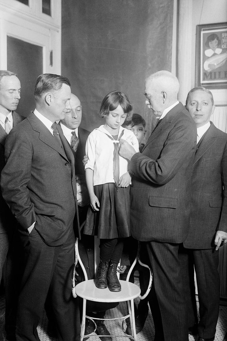 A girl stands on a chair surrounded by men while a man puts a button on her shirt.