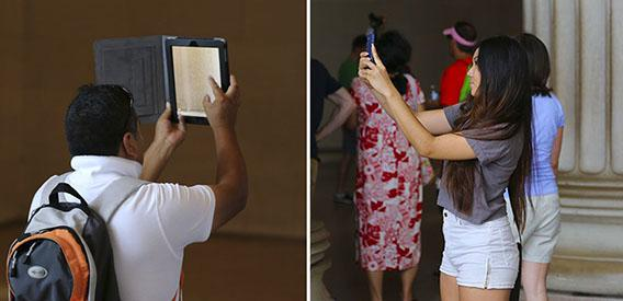 Two visitors to the Lincoln Memorial using their Apple Products.
