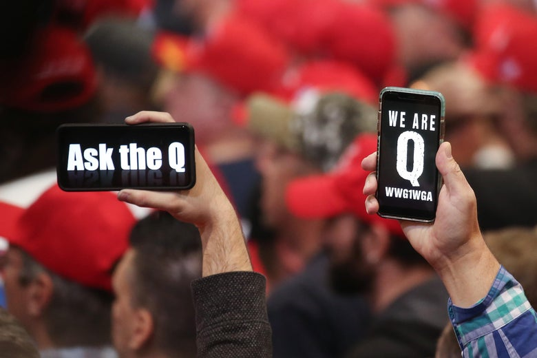 Trump supporters hold up phones displaying QAnon slogans, a sea of red MAGA hats in the background
