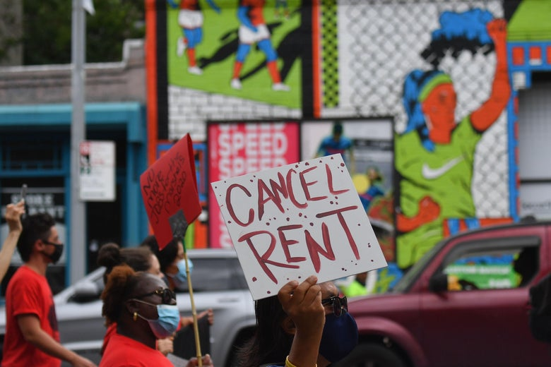 "In a protest, a hand holds up a sign saying ""Cancel Rent."""