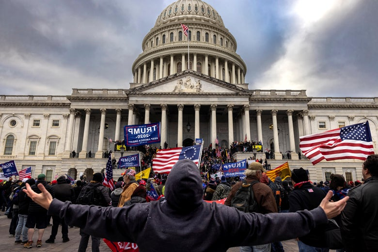 A man in a hoodie stands extending both arms straight out to his sides in front of a crowd of flag-bearing Trump supporters storming the Capitol.