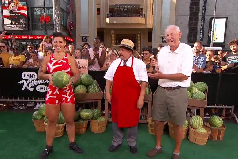 Kortney Olson, Guillermo Rodriguez, and a civilian standing in front of a watermelon stand.