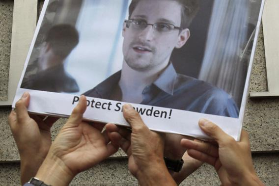 Protesters supporting Edward Snowden, a contractor at the National Security Agency (NSA), hold a photo of Snowden during a demonstration outside the U.S. Consulate in Hong Kong June 13, 2013.
