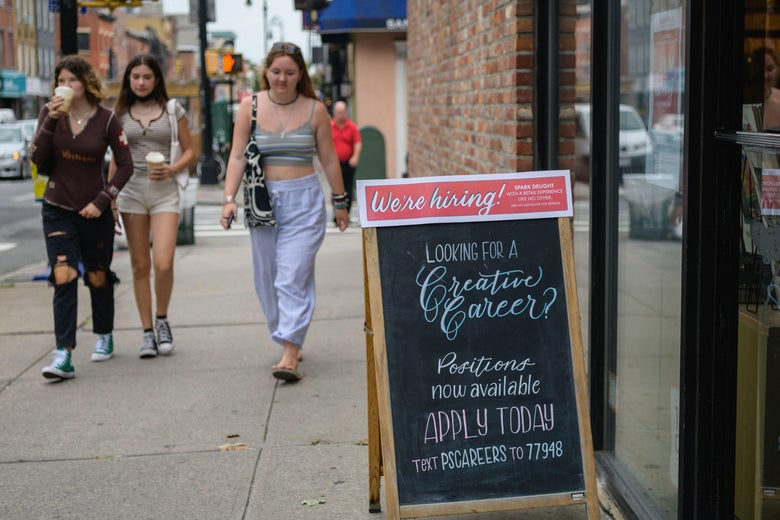 """A group of young people walk past a """"We're hiring!"""" sign posted at a store in New York City on August 20, 2021."""