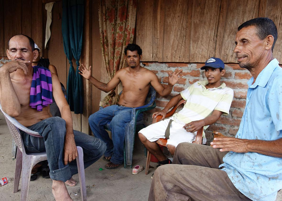 Four papaya farmers discussing the canal over a bottle of rum.