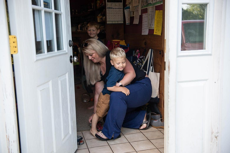 View from outside into Heather's mudroom, where she helps one son take off his shoes as her other son smiles at the camera