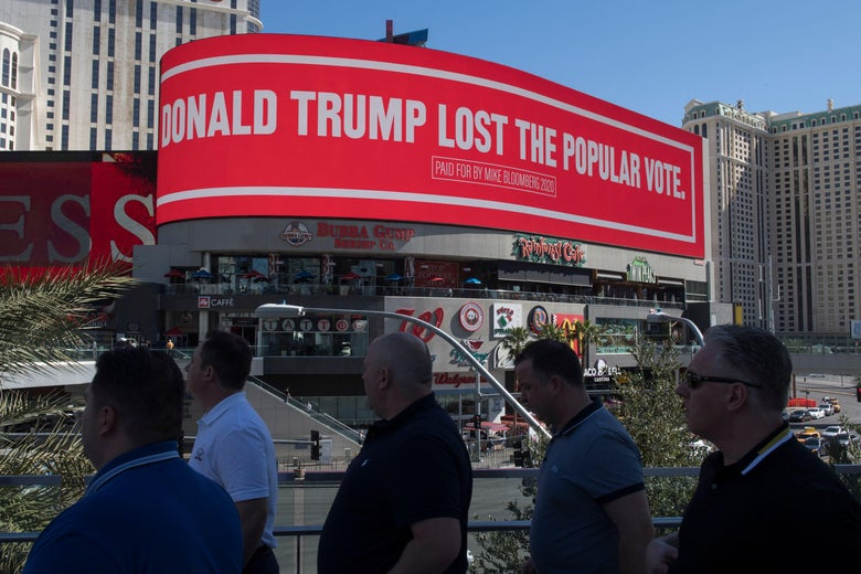 People walk by a second billboard paid for Mike Bloomberg, saying Trump lost the popular vote.