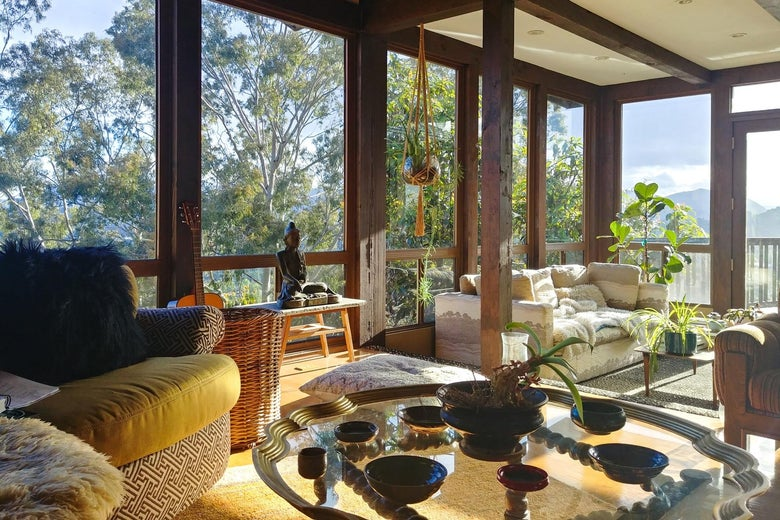 A warm living room with a view of trees and mountains.