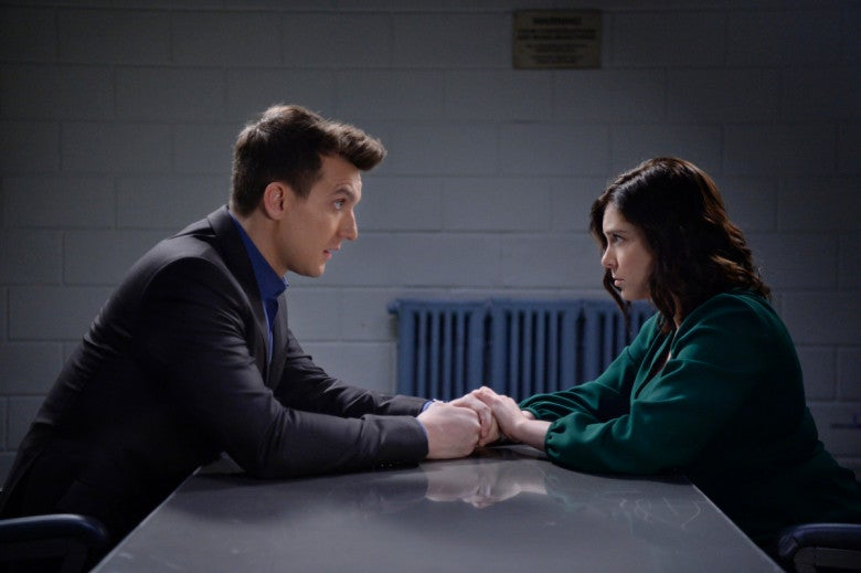 Scott Michael Foster as Nathaniel and Rachel Bloom as Rebecca hold hands in an interrogation room