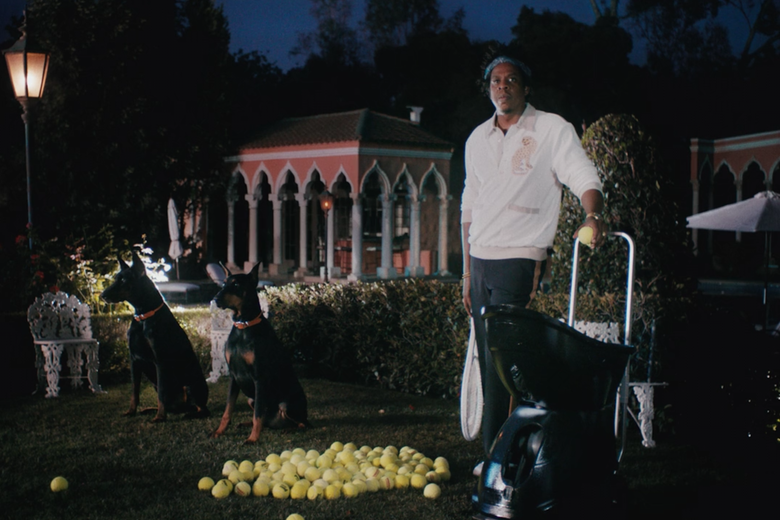 Jay-Z, in tennis gear and holding a racket, stands next to a mound of tennis balls, two dogs, and a ball machine.