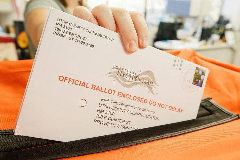 A employee at the Utah County Elections Office puts mail-in ballots into a container.