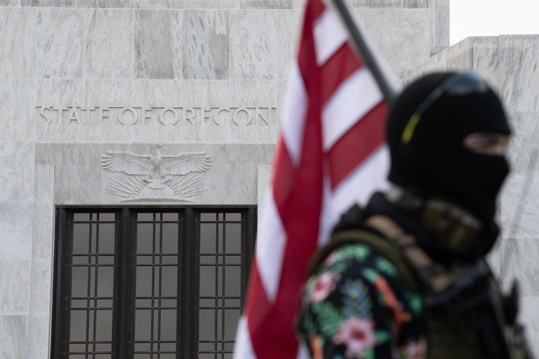 A man in a Hawaiian shirt and balaclava holds an American flag in front of the Oregon State Capitol