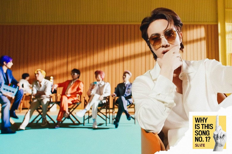 A man sits facing the camera. He has brown hair, a white suit, and sunglasses. Behind him is a yellow wall with orange panels and a group of five men. They are in brightly colored suits and sitting in director's chairs. The carpet beneath them is turquoise.