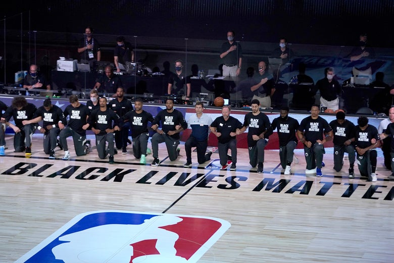 Bucks and Celtics kneel on the bubble court by the Black Lives Matter logo.