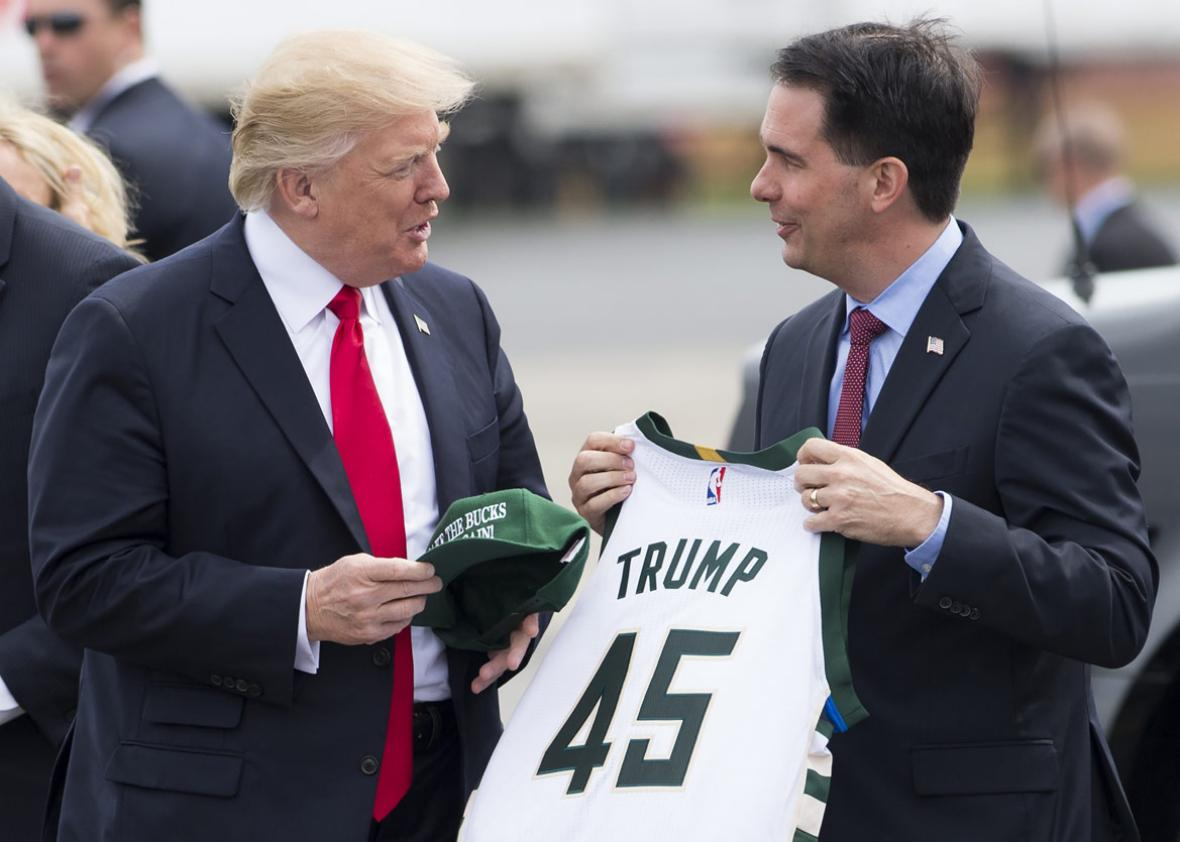 US President Donald Trump holds a hat reading, 'Make the Bucks Great Again,' given to him by Wisconsin Governor Scott Walker (R)