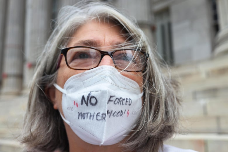 """Debra Sweet, wears a mask inscribed with the words """"No Forced Motherhood"""" as she joins people gathered for a reproductive rights rally at Brooklyn Borough Hall on September 1, 2021 in Downtown Brooklyn in New York City."""