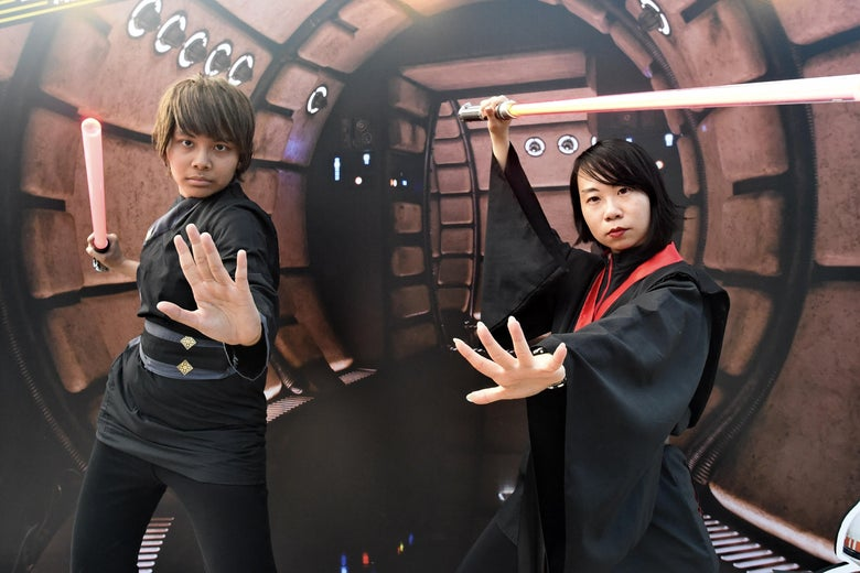 Two people in robes wield lightsabers.