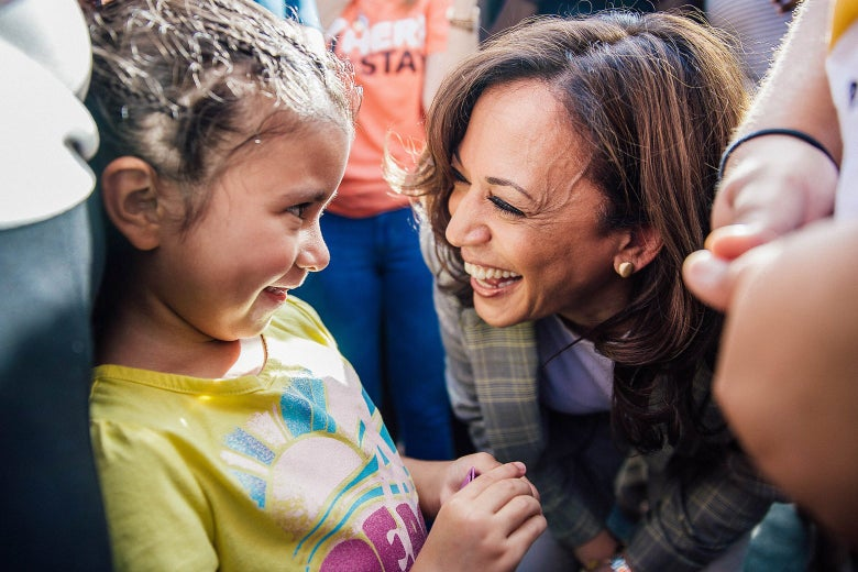 Sen. Kamala Harris smiles and leans down to talk to a young immigrant child.