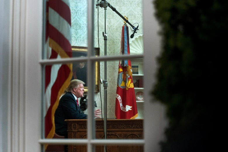 President Donald Trump, seen through the window, speaks to the nation in his first-prime address from the Oval Office of the White House.