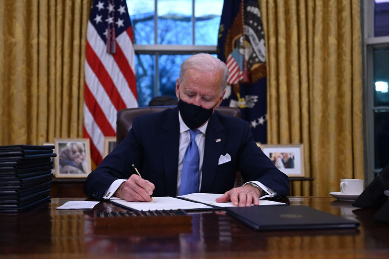 Biden sits in the Oval Office and signs orders.