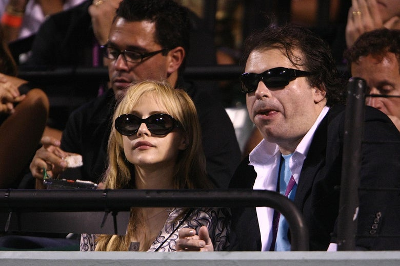 A woman, left, wears black sunglasses and a pink shirt. She is seated with a man, right, in a black jacket, pink button down shirt, and blue t-shirt; he also wears sunglasses. They are looking out onto a tennis court off-camera.