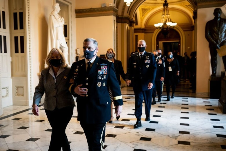 Milley, wearing a uniform and a mask, walks with his wife through a tiled hallway.