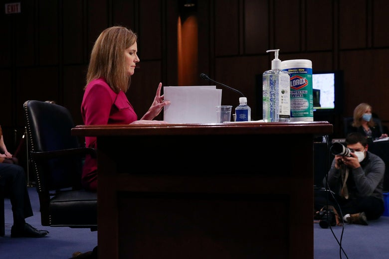 In profile, Amy Coney Barrett sits at a desk and reads a paper.