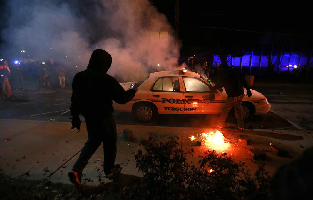 A protester videos a police car set on fire by protesters in Ferguson, Missouri, Nov. 25, 2014