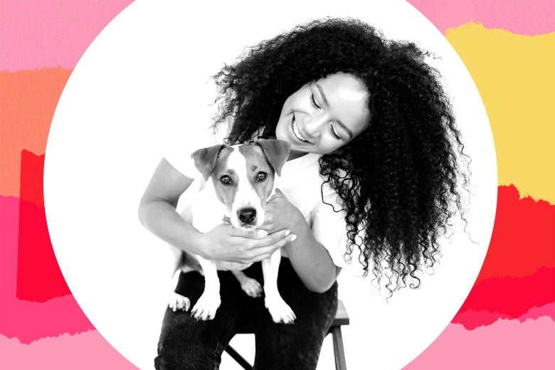A woman with long, curly hair sitting on a stool with a terrier on her lap.