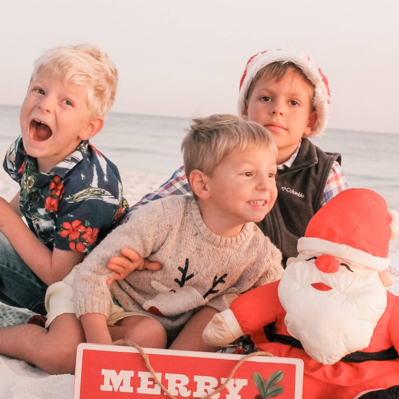 Oliver, Henry, and Teddy sitting on the beach posing with a little Santa and 'Merry Christmas' holiday sign.