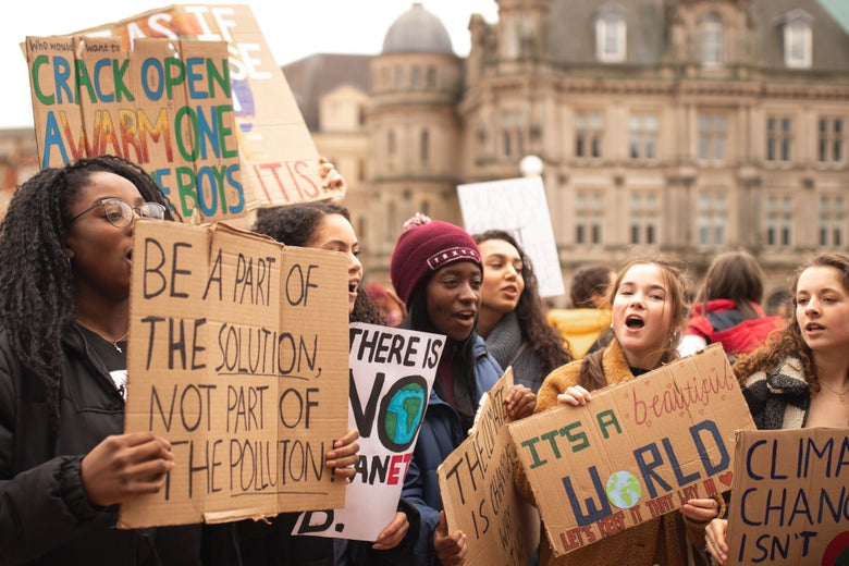 """Women stand outside holding protest signs that say: """"Be a Part of the Solution, Not Part of the Pollution"""" and """"It's a Beautiful World."""""""