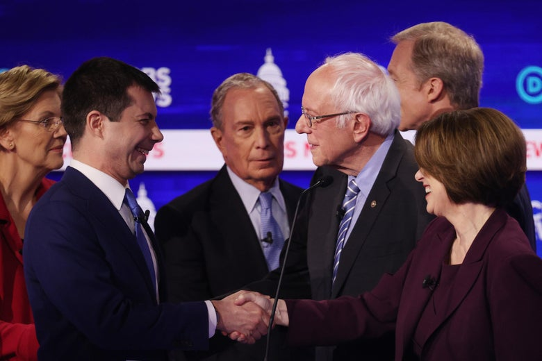 The candidates greet each other on the debate stage. Buttigieg and Klobuchar shake hands, both smiling.